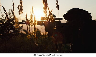 Armed man taking aim at sunset. Airsoft