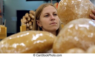 young woman taking bread from shelf in bakery. She chooses...