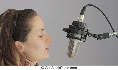 Girl sings in the studio microphone - Woman expressive move,...