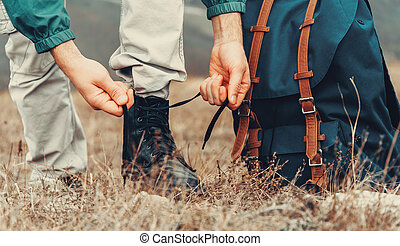 Hiker man tying shoelaces on nature outdoor, near backpack...