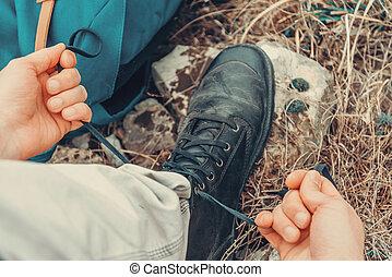 Traveler man tying shoelaces on nature - Hiker man tying...