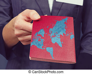 Woman holds out a passport. Map of the world painted on the...