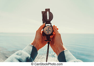 Traveler holding a compass on background of sea