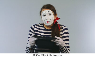 Woman mime gets dollars from hats. Concept: Purchase of unexpected