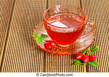 rose hip tea with fresh berries on the wooden background