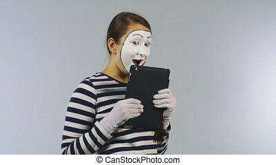 Woman mime with a tablet gadget