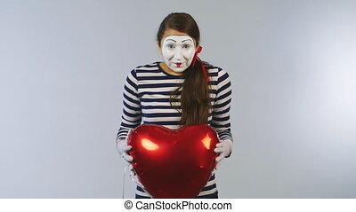 Cheerful girl with a ball showing a heartbeat. The concept of love, Valentine's Day