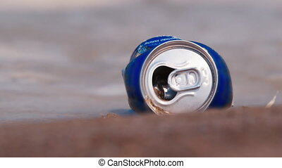 An empty beer can in the dirty water. Water pollution