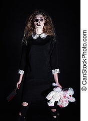 Horror shot: strange gothic girl with torn rabbit toy and bloody knife in hands