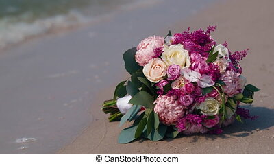 Bridal bouquet lying on the sand