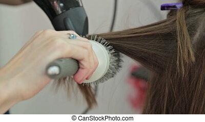 Hairstylist with brush and dryer hairdresser drying hair of...