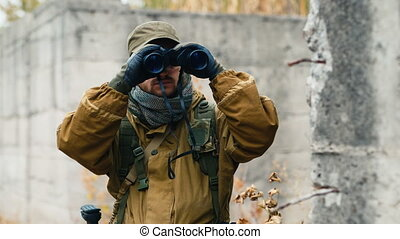 Man in camouflage looking through binoculars
