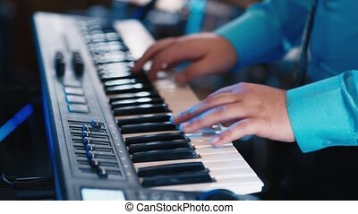 Hands of the musician playing on a synthesizer, an...
