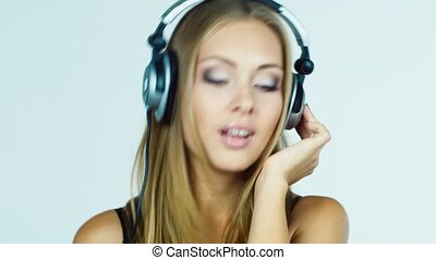 blonde girl listening to music on headphones and dancing intensively