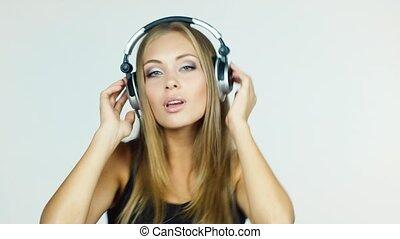 Blonde in headphones emotionally listens to music: rhythmic dances