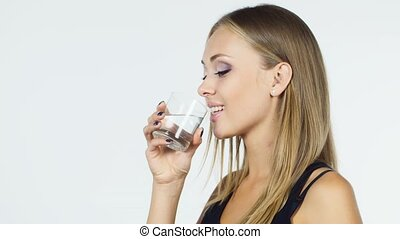 Attractive blonde woman drinks water on a white background