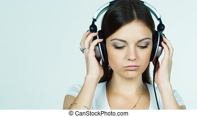 Attractive dark-haired girl puts on headphones and listening to music
