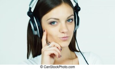 Dark-haired woman listening to music on headphones and flirting at the camera