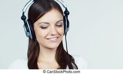 Dark-haired girl with headphones in the flirting camera