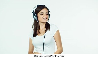 Attractive girl dancing with headphones on a white background