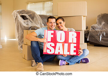 moving couple holding for sale sign at home