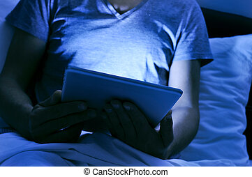 young man using a tablet in bed at night - closeup of a...