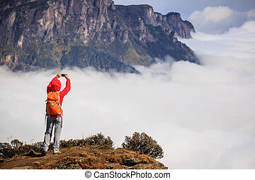young woman hiker taking photo with smart phone on mountain...