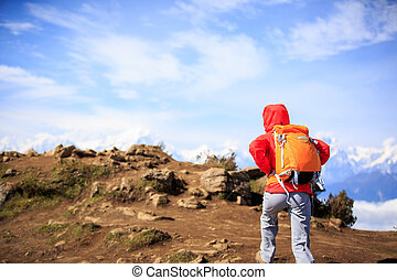 young woman hiker hiking on beautiful mountain peak