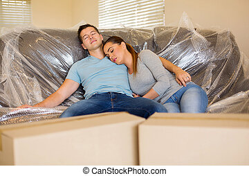 couple resting on couch in new home - tired couple resting...