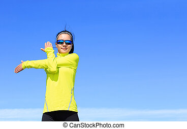 young fitness woman runner stretching arms before running on...