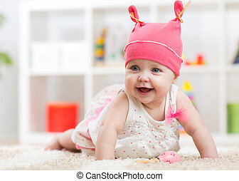 Smiling baby child crawling on nursery floor