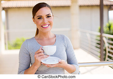 young woman drinking coffee on balcony