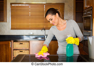 young woman cleaning the stove - smiling young woman...