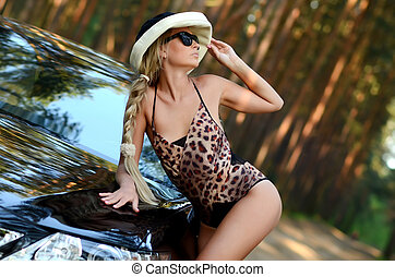 sexy beautiful woman with blond hair posing in black luxury car