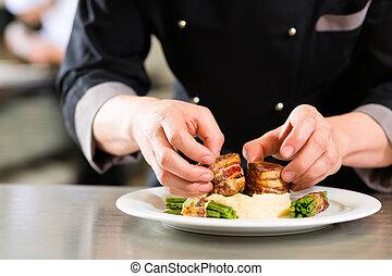 Chef in restaurant kitchen preparing food - Chef in hotel or...