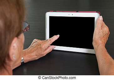 Senior lady relaxing and reading the screen of her tablet,...