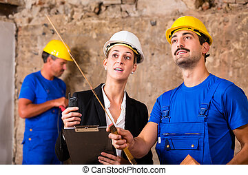 Builder and architect discussing on construction site, he is...