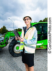 architect in front of excavator using pad or tablet