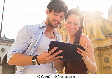 Young Tourists in city with tablet computer