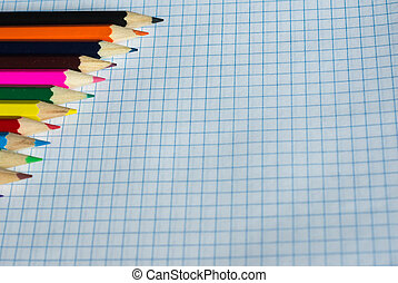 Pencils of different colors on an open notebook