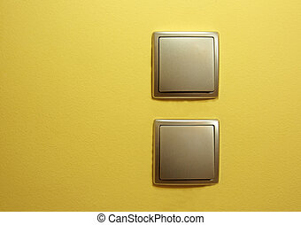 Two flat silver power switch, one below the other on the yellow wall in the room