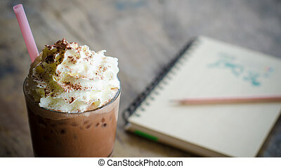 iced cocoa in a glass and note book