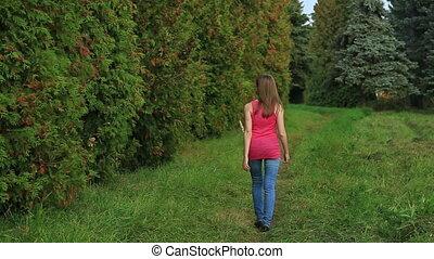 Girl walking away through green alley, HD
