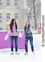 Women ice-skating holding hands - Two young brunette women...