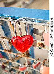 Red padlock in heartshape on rusty fence