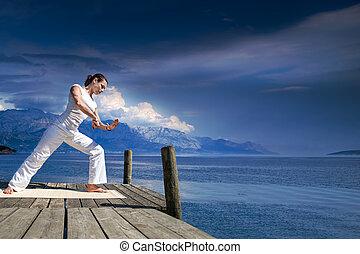 tai chi - young woman making tai chi exercise at a lake