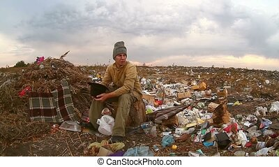 man homeless beggar sitting in a landfill with a hat asks...