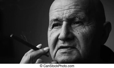 Old grandfather smokes a cigar closeup - Old grandfather...
