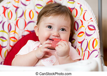 Baby with teething ring sitting in craddle
