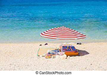 Resting place in the sun - Red striped sun umbrella and some...